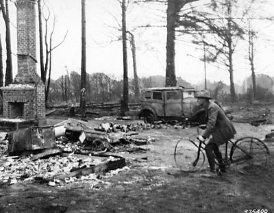Man pretending to ride a burned-up bicycle in the ruins of Bandon, 1936