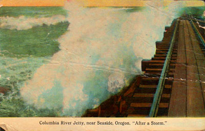 "A wave breaks over South Jetty in this colorized picture postcard image from the 1910s. This railroad line is the one used to rescue the crew of the shipwrecked schooner ""Admiral"" after a wave wedged it into the unfinished jetty."