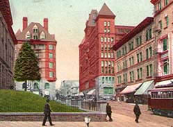A view of the Portland Hotel across the lawn from the Pioneer Courthouse, circa 1920, with a streetcar on the right.
